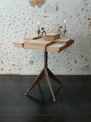 Per me e per pochi, conversation table (old books, un-used chair, iron, candles) - courtesy JAMESPLUMB